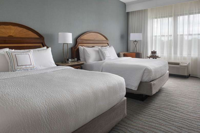 hotel guest room with two beds with white covers