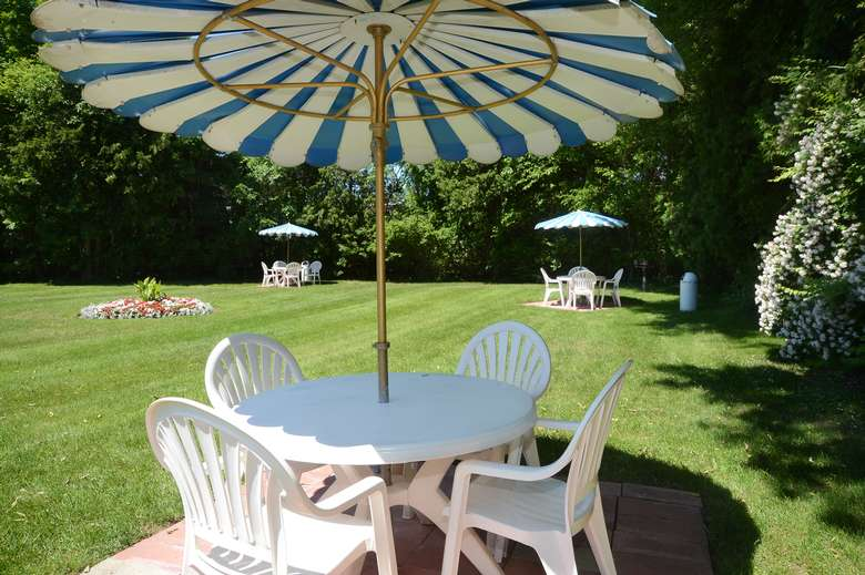 plastic table and four chairs with a striped umbrella