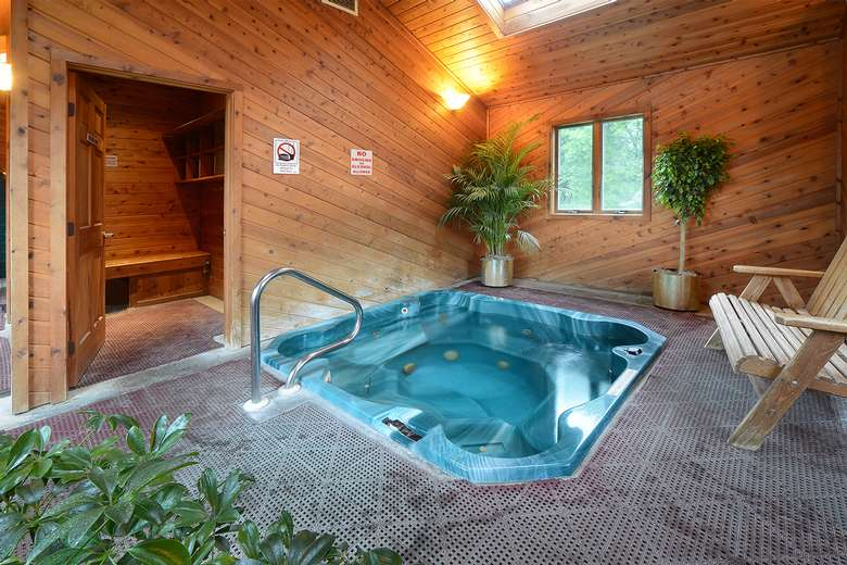 teal hot tub in a wooden room with the entrance to a sauna next to it