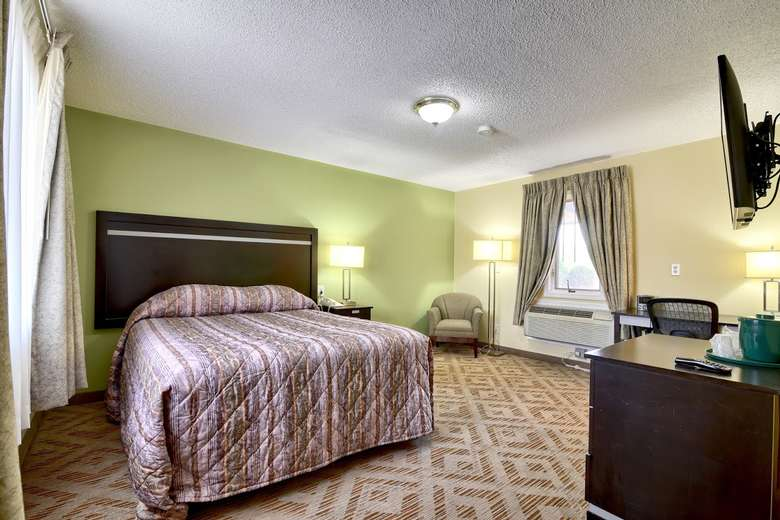 a fairly open hotel bedroom with a bed on one side and a desk near the front