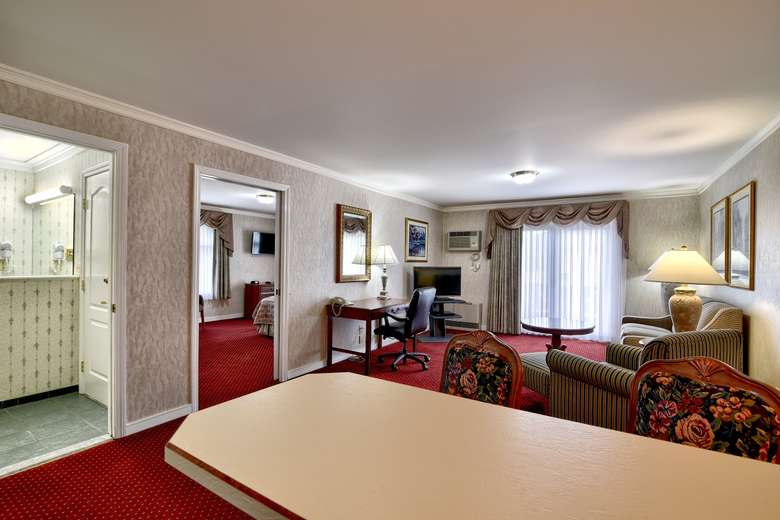 a living area with a red carpet inside a large hotel suite with multiple rooms