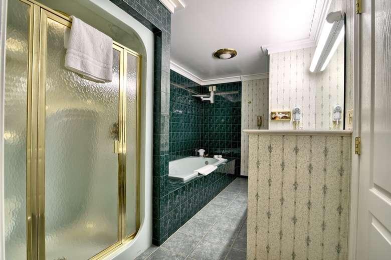 a glass enclosed shower next to a bathtub