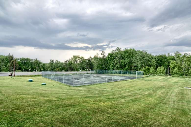 a large green lawn with a big tennis court