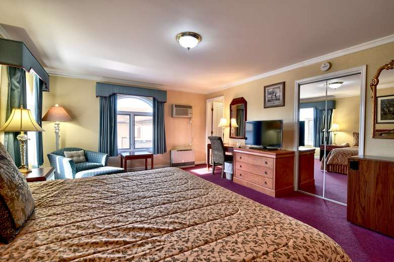 a hotel suite with a window on one side, a large bed, a chair in the corner, and more