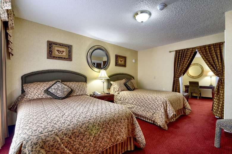 two large beds inside a hotel bedroom with a red carpet