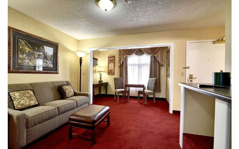 lounge space in a hotel suite with red carpeting and sofas