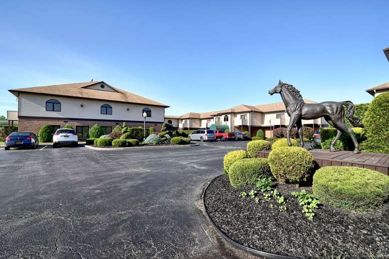 a horse statue outside near a parking area for a hotel