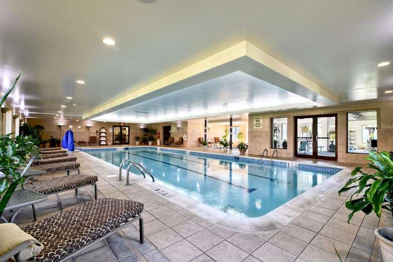 a large rectangular indoor pool with lounge seating along the side