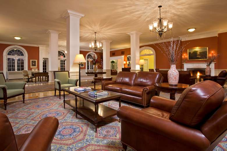 hotel lobby with brown leather couches, green chairs, and tall white columns