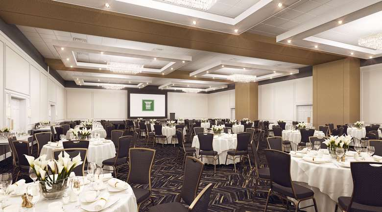 ballroom with round tables and white tablecloths set up for a meeting or event