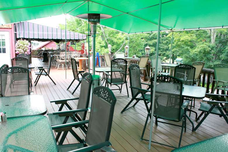 outdoor porch with tables and chairs under a green tent