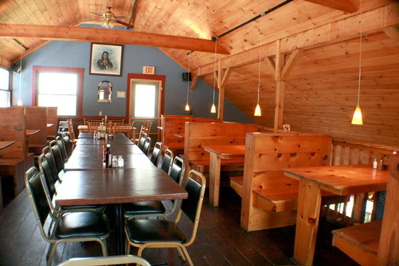 restaurant tables, chairs, and booths in a room with wood panels