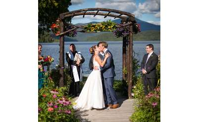 bride and groom kissing under the cedar arbor, water in the background
