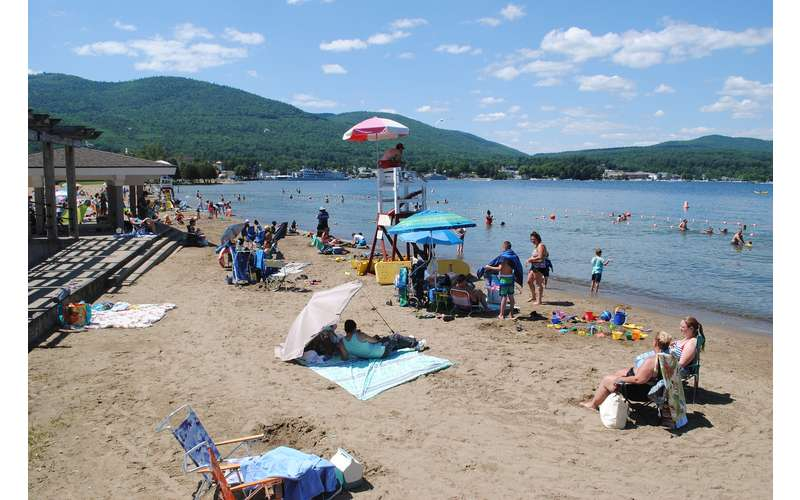 lifeguard chair and people on the sandy beach in lake george
