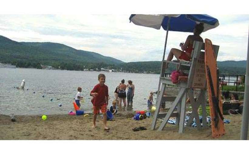 Kids playing in the sand near a lifeguard station on Lake George