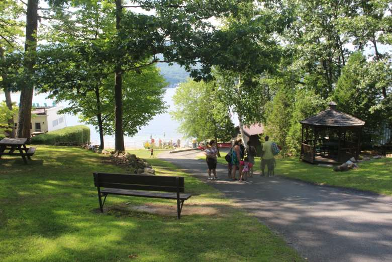 A paved walkway leading down to a beach with a bench and green grass