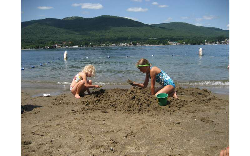 Two girls playing in the sand at Usher's Park Beach with lake george and mountains in the background