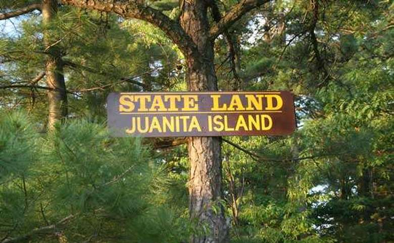 the sign for the juanita island state land on a tree