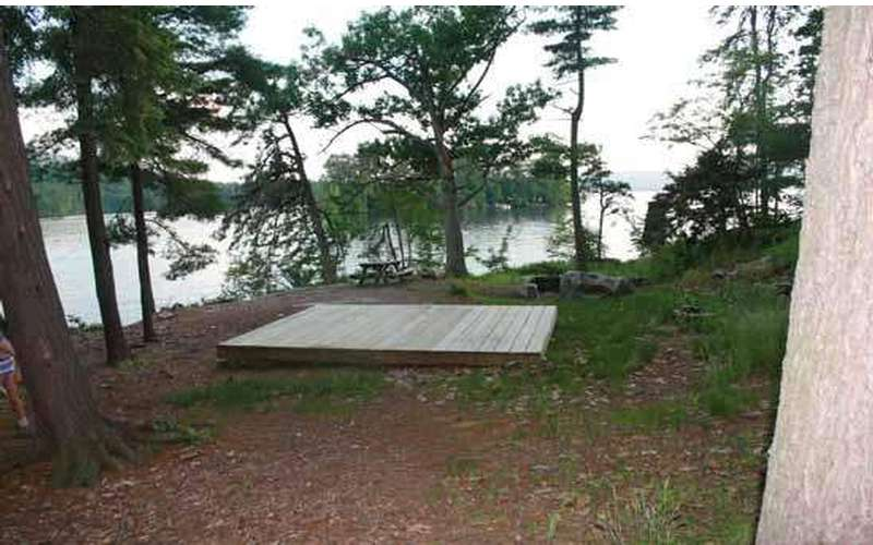 a large and wooden tent platform on flat ground in the woods