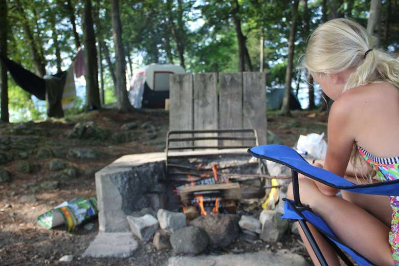 a girl is roasting hot dogs over a fire at a campsite