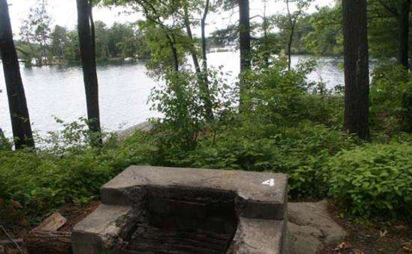 a firepit at a campsite with the lake in the background