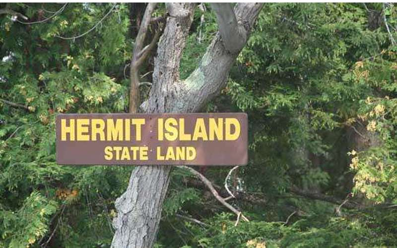 the sign for hermit island state land on a tree