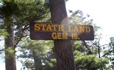 a sign for gem island on a tree