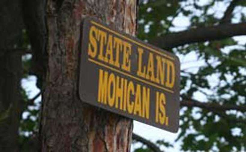 the sign for mohican island on a tree