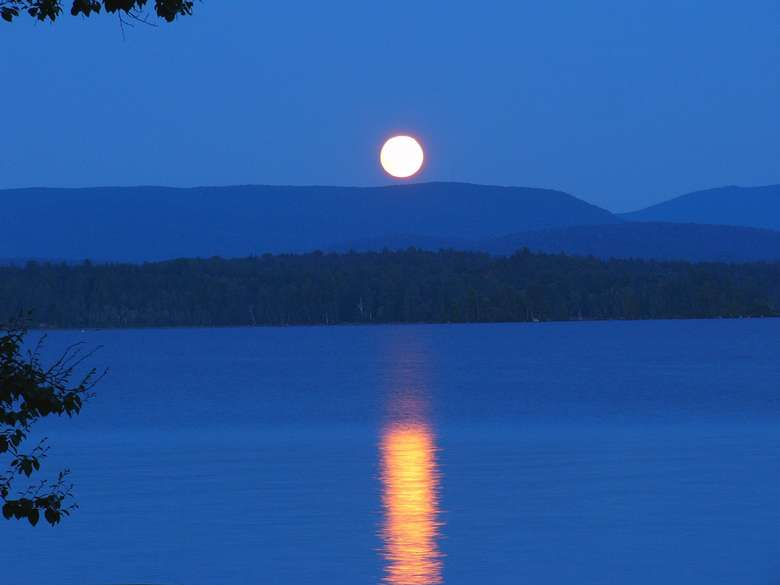 full moon reflected in the waters of long lake
