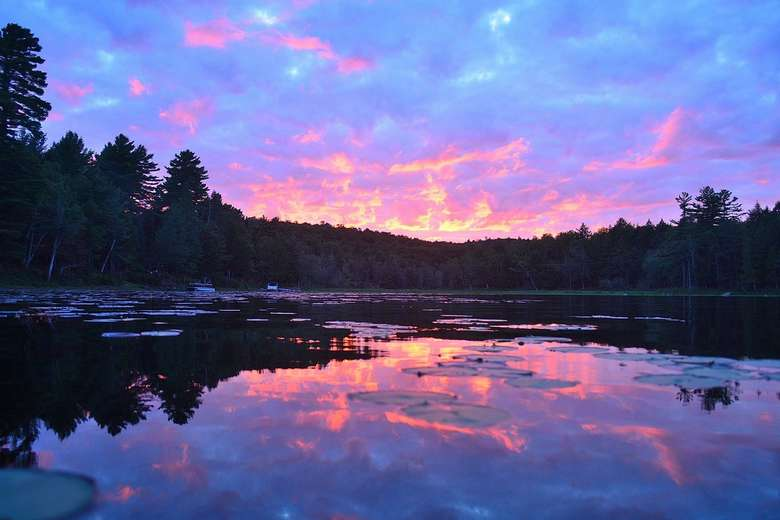 purple and pink sunset reflected in the waters of long lake