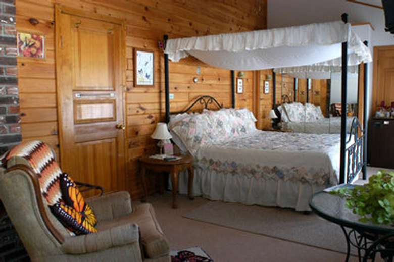 a four poster bed in a wood paneled room with a white bedspread