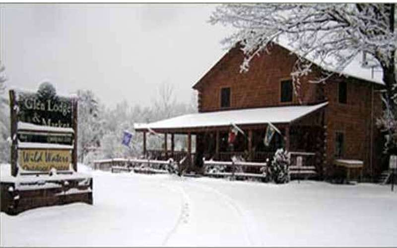 the lodge in the winter with snow, the sign in front of the lodge