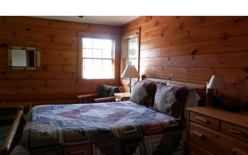 a bed in a bedroom with wood paneled walls