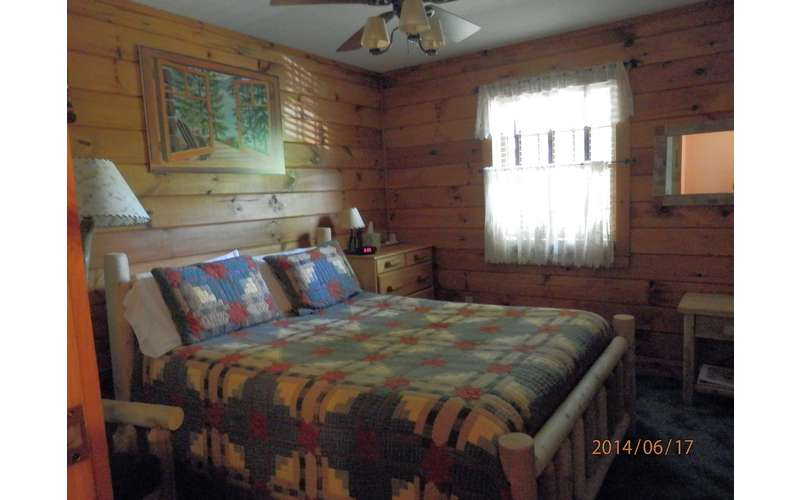 a bed in a bedroom with a patterned bedspread