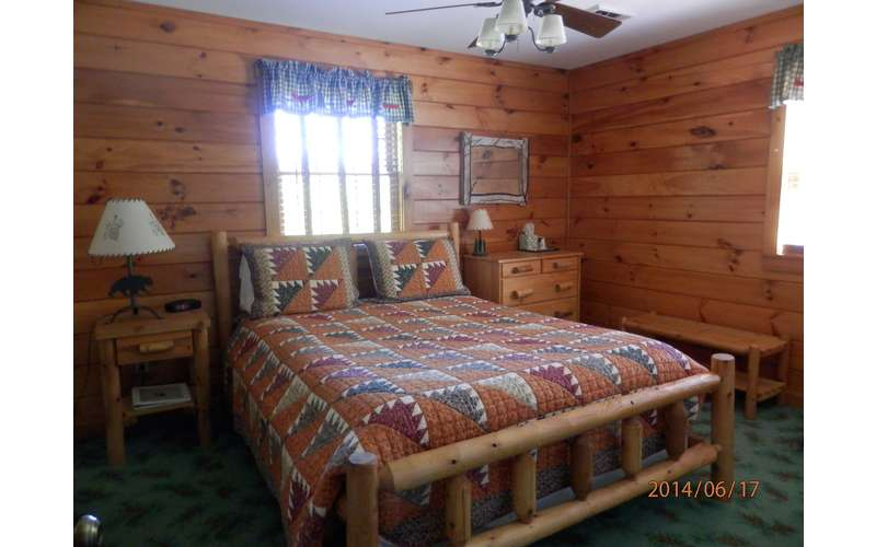 a checkered bedspread in a wood paneled bedroom