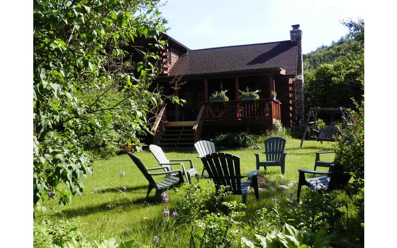 Adirondack chairs outside in a circle, lodge in the background