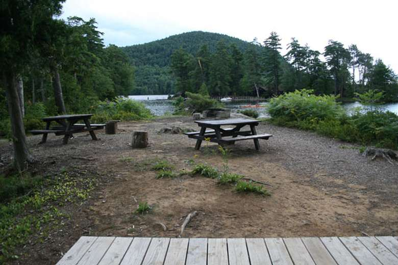 a campground area with a tent platform and two picnic tables