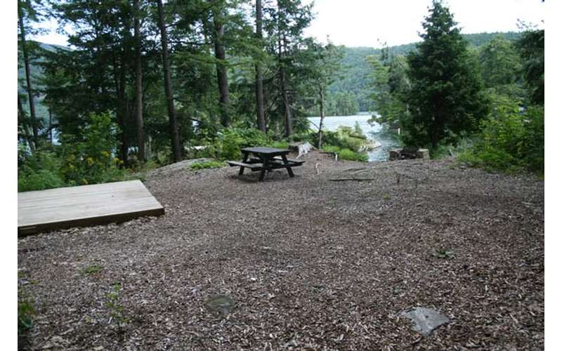 a flat area with a tent platform and a picnic table