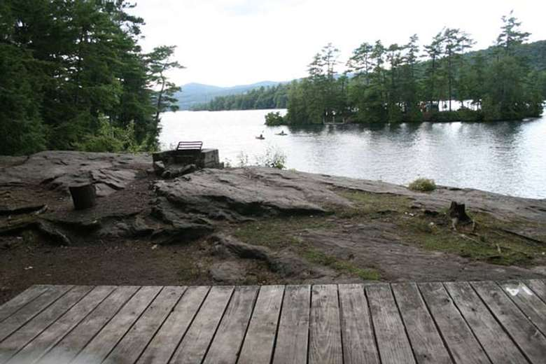 a tent platform located near the rocky shoreline of a lake