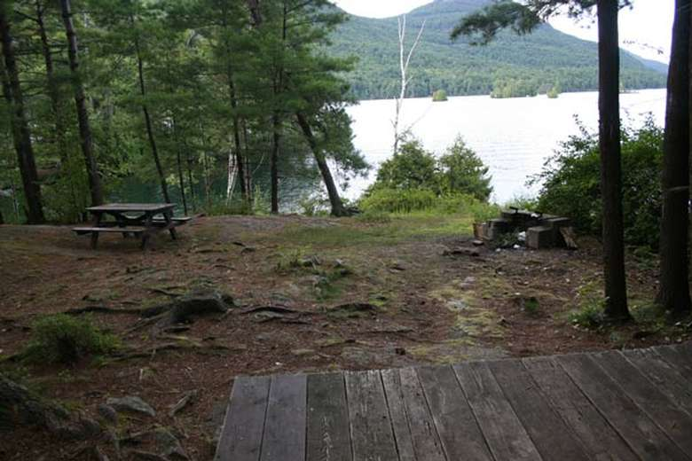 a picnic table, tent platform, and grill near the waterfront