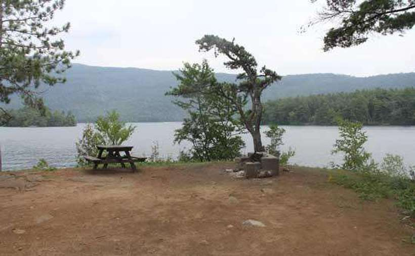 a fairly clear campsite with a picnic table with the lake in the background