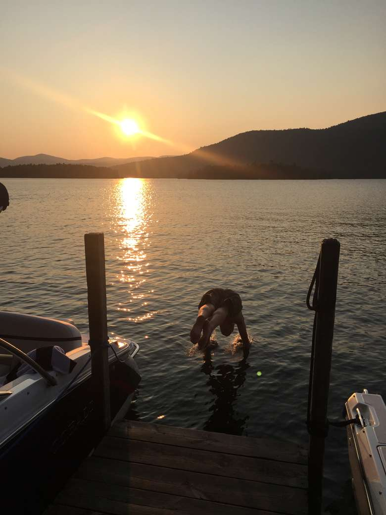 a person diving into the water between two docks during sunset