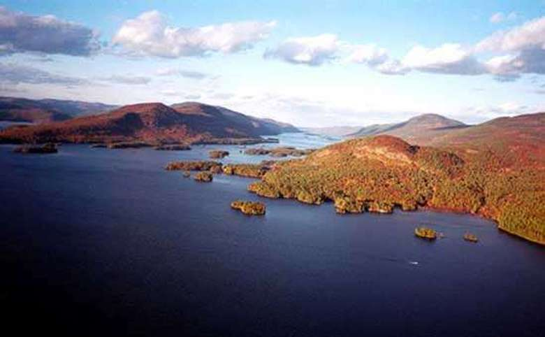 an aerial view of small islands on a lake and trees with fall foliage all around