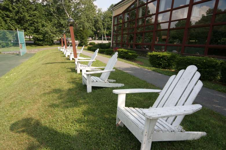 row of white adirondack chairs outside