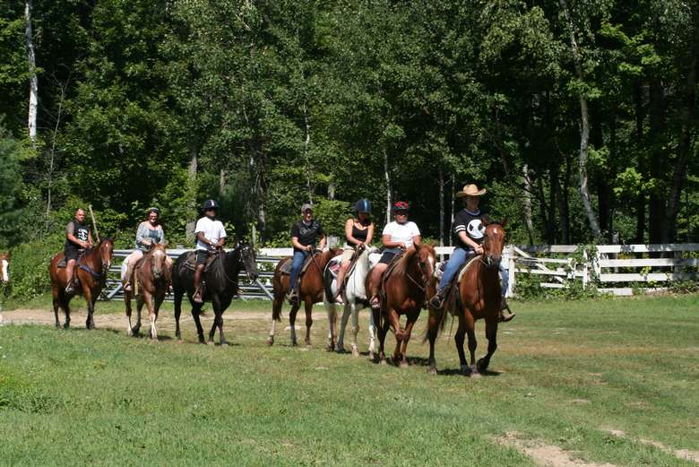 people on a guided horseback trail ride