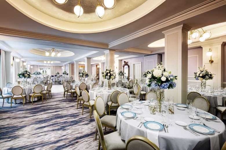 a spacious ballroom with tables and decor
