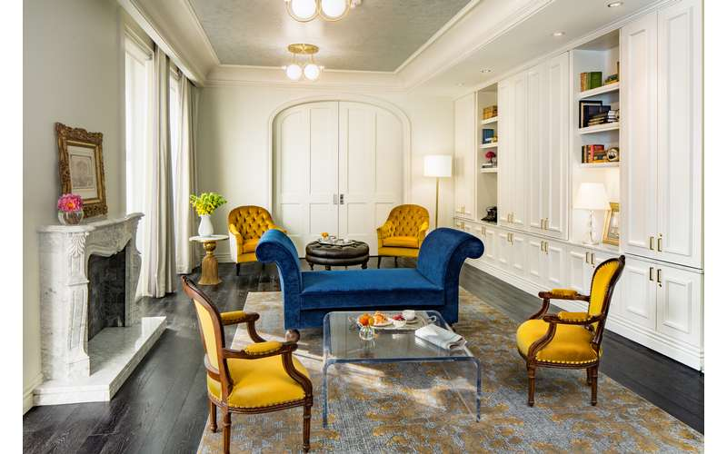 a library room with yellow chairs and blue furniture
