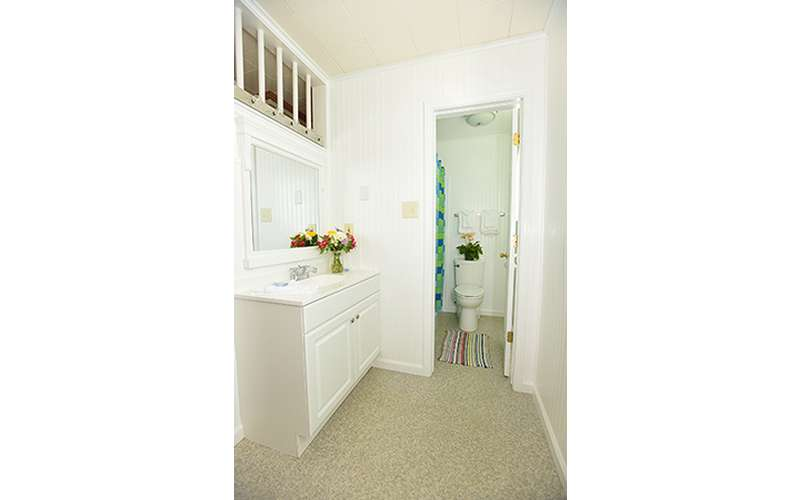 a bathroom area, all white walls and cabinet