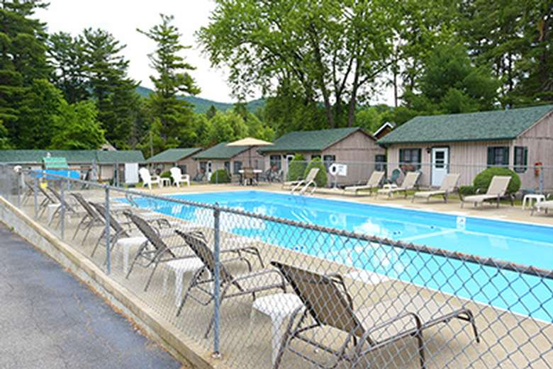 an outdoor pool with pool chairs lined up