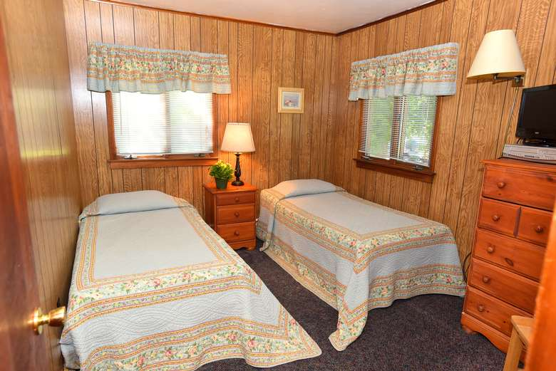 two beds in a small bedroom, dresser